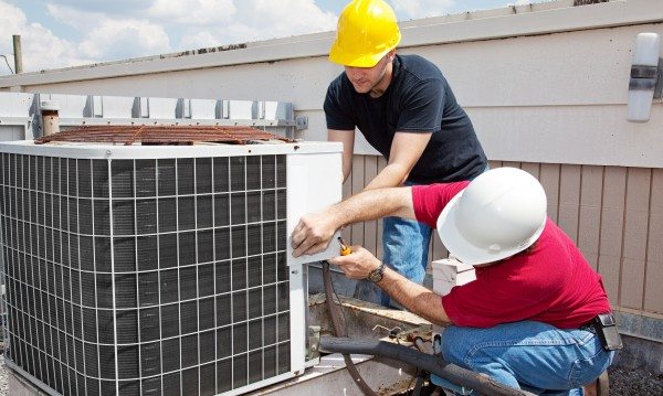 Two workers on the roof of a building working on the air conditi